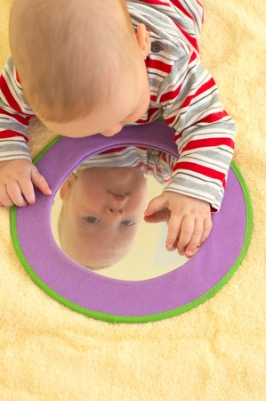 Baby boy plays with toy mirror photo