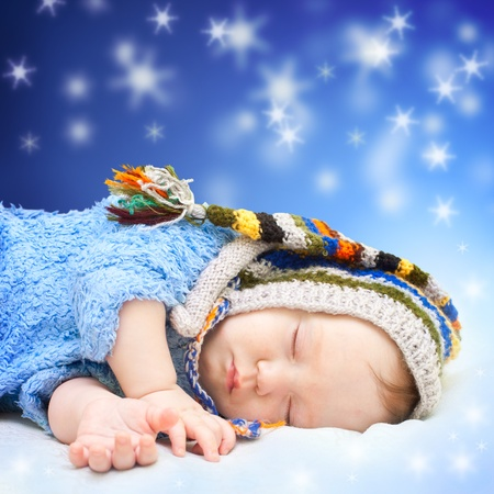 dwarf christmas: Baby sleeping in cute hat. Magic night sky background. Stock Photo