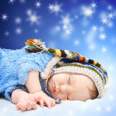 estrella de la vida: Bebé durmiendo en lindo sombrero. Noche mágica del cielo de fondo. Foto de archivo