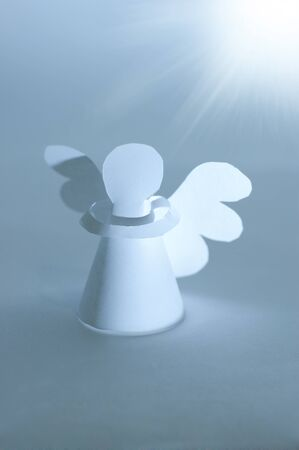 Handmade angel cut out from  paper at bright star lighting. Religion concept. photo