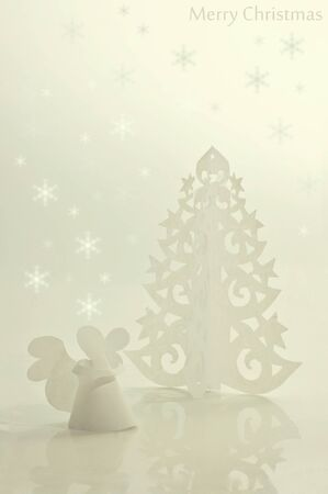 Handmade angel and Christmas tree cut out from office paper photo