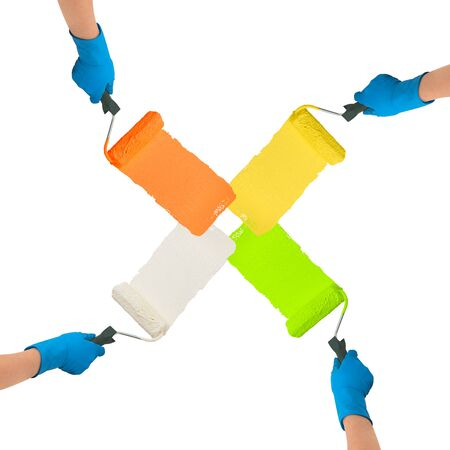 multycolored: Hands with rollers dipped in bright colors paint each other trace on white background