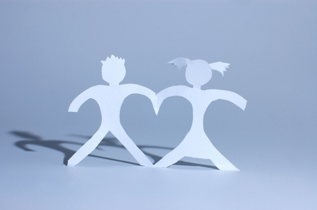 Paper girl and boy holding on hands and forming heart between figures photo