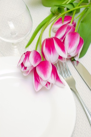 Tender pink tulips grace a table setting . Sample copy space provided with the empty white plate photo