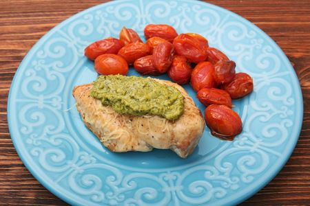 tasty baked chicken breasts covered with basil pesto sauce