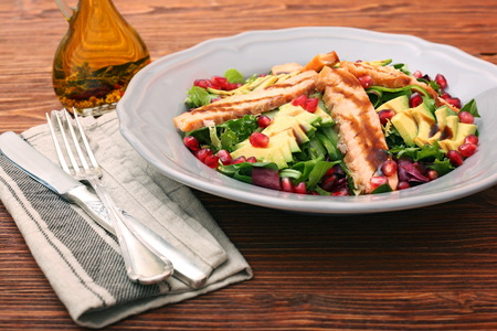 Salad with fried salmon, avocado and pomegranate seeds Stock Photo
