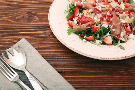 Arugula salad with strawberries, feta cheese, prosciutto, parmes