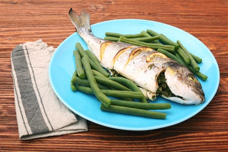 Grilled sea bream fish with green beans on wooden background Stock Photo