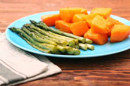 Baked asparagus pumpkin on plate on wooden background