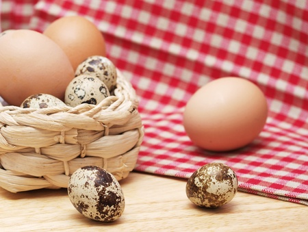 Quail and hen eggs on kitchen table with a towel photo