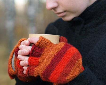 Woman in bright red mittens holding a hot drink Stock Photo - 16131093