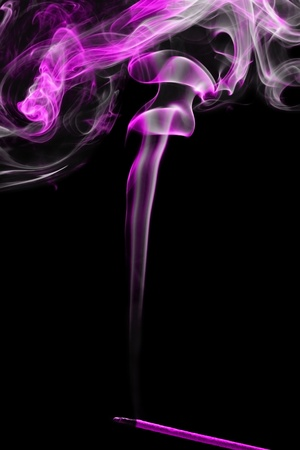Pink smoke coming up from an incense stick over a black background photo