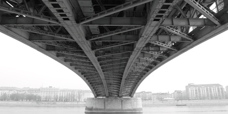 zwart-wit foto van een abstracte stalen constructie onder de brug