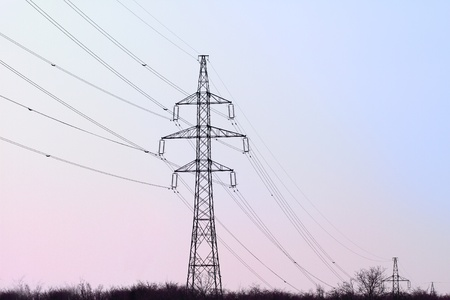 electricity pylon with many cables on blue and purple sky photo