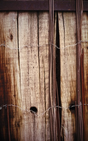 Old board fence with rusty nails and a barbed wire photo