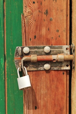 old lock on the wood door of color brown and green photo