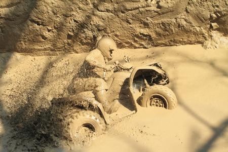 jonge man zwaar vast in de modder met zijn quad Stockfoto