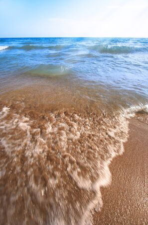 Beach pebbles under clear water with waves photo
