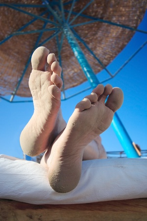 Closeup of man foot with sand and blurred people on the beach. Stock Photo - 10919499