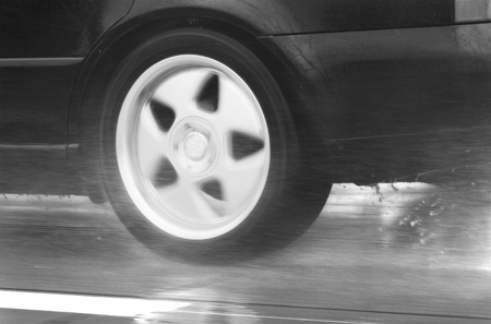 wheel of speeding sport car driving fast in a rainy day photo