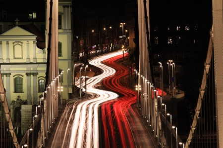 suspension bridge at night with motion blurred car lights photo