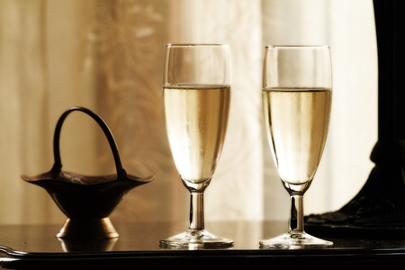 Two glasses of champagne on abstract yellow background photo