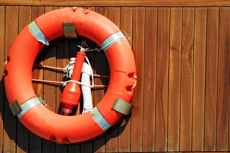 Lifebuoy hanging on wooden wall Stock Photo
