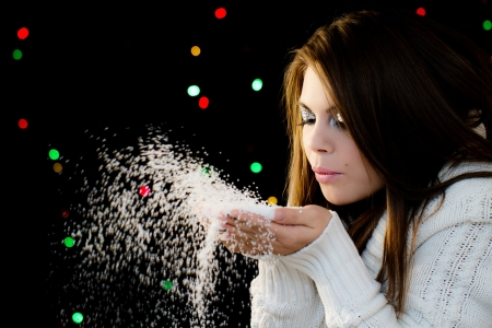 Beautiful girl blowing white snowflakes from her hands photo