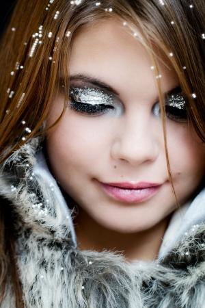 maquillaje de fantasia: Mujer joven en un abrigo peludo cubierto de nieve