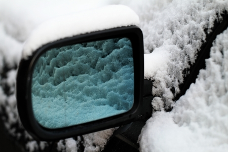 Snowy car from the mirror  close up  photo