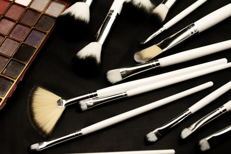 Brushes and make up eye shadows (dark background) photo