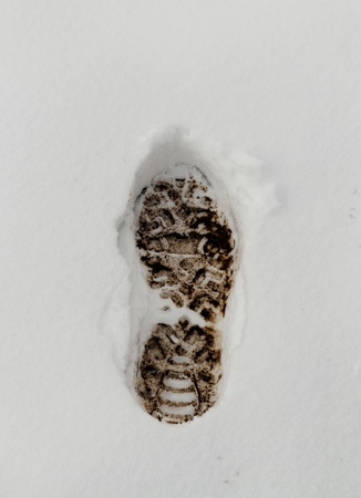 mud and snow: Muddy Footprint in the fresh white snow Stock Photo