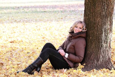 Beautiful woman portrait outdoors leaning on a tree photo
