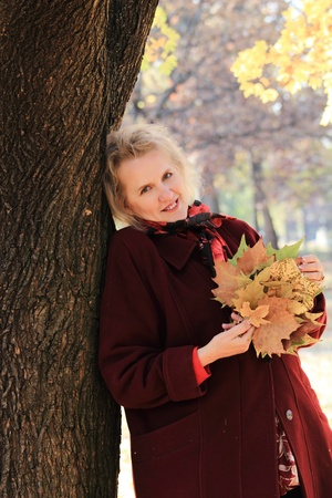Portrait of elderly woman with maple leaves in autumn park photo