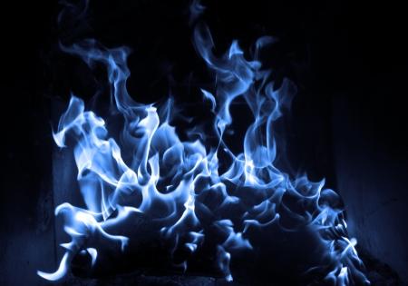 Blue flame isolated on dark background photo