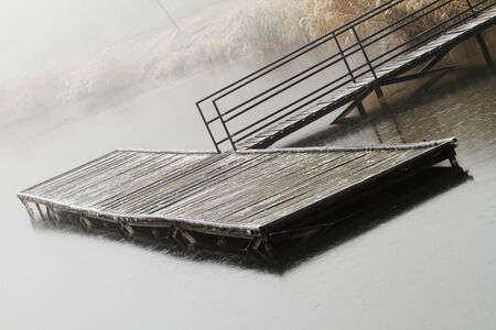 Wooden dock in a lake. Photo taken in a misty day photo