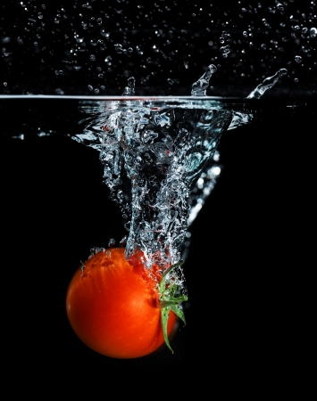 Fresh tomato dropped into water, isolated on dark background  photo