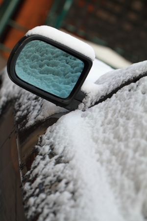Snowy car from the mirror (close up) photo
