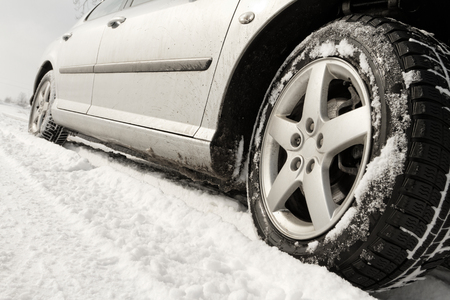 winter road: Close up of a cars tires on a snowy road