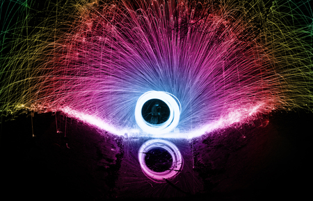 Showers of hot glowing sparks from spinning steel wool. photo
