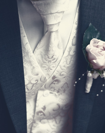 Groom with tuxedo and wedding flower - close-up photo