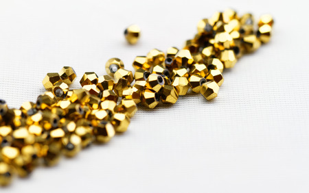 drilled: Beautiful golden glass beads closeup on white background Stock Photo