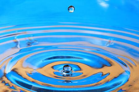 orange water: Blue- orange water drop splashing with waves Stock Photo