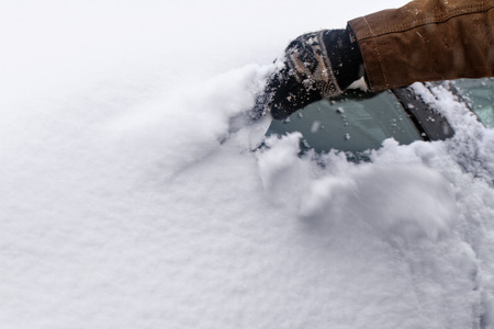 defrost: Man scraping snow and ice from car window