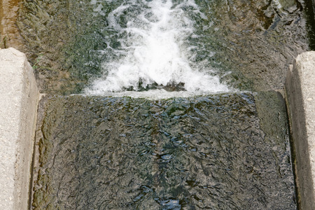 runoff: Large cement sewer drain pipe emptying into river Stock Photo