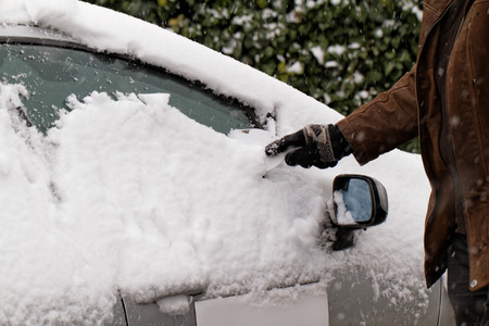 scraping: Man scraping snow and ice from car window