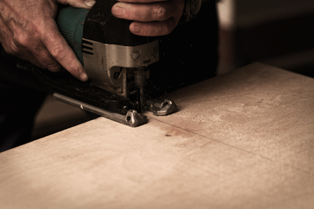 fret: Photo of a man working with fret saw