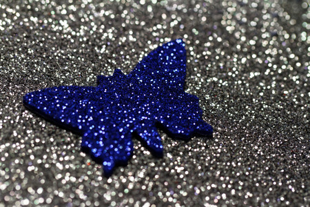 Blue butterfly decoration on silver background - macro photo