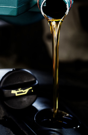 oil change: Fresh oil being poured during an oil change to a car