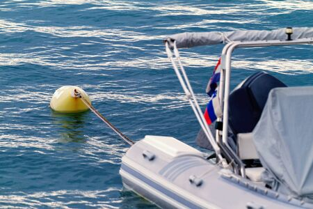 White motorboat with yellow buoy - detail photo